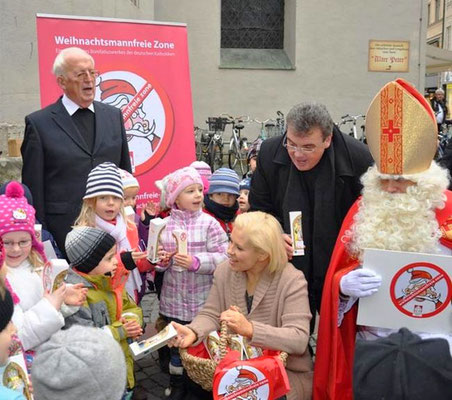 """Maite Kelly verteilt mit Msgr. Georg Austen Schokonikoläuse an die Kinder. Rechts im Bild ist auch ein """"richtiger"""" Nikolaus mit Mitra zu sehen."""