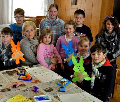 Maite Kelly sitzt an einem Maltisch, umgeben von Kindern, von denen drei einen selbstgebasteltet Hasen in der Hand halten.