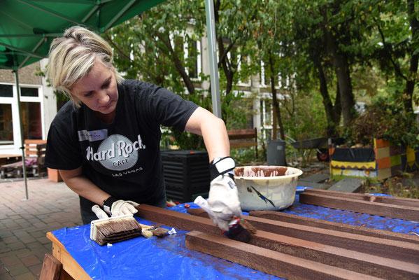 Kerstin streicht die Holzpfähle für die Kompoststelle  © Theresa Meier