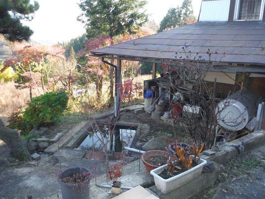 母屋から蔵を見る。池がある。