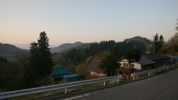 県道から見下ろしたところ。左の青屋根はお隣さん。南東向きに開けている。