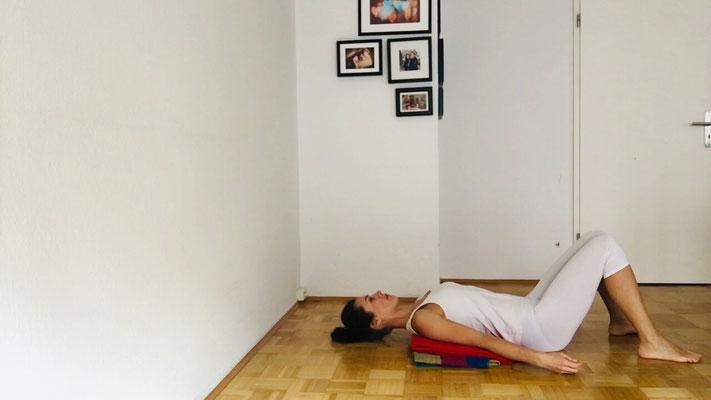 Nacken entspannen: nicht zu weiche Decke(n) übereinander legen. Mit Schultern auf die Decken legen. Kopf liegt am Boden.