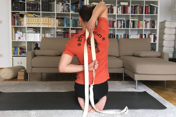 8// Gomukhasana: strecke die Arme zur Seite und bring die li. Hand zum Rücken. Strecke den re. Arm nach oben und beuge ihn bis sich die Hände hinter dem Rücken berühren (Gurt). Wachse mit der Kopfkrone nach oben... Seitenwechsel.