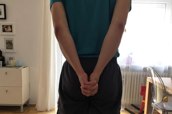 4// Vorbereitung: Stehe aufrecht, Füsse hüftweit. Roll die Schultern nach hinten und bring die Hände hinter dem Rücken zusammen, so daß sich die Handinnenflächen berühren...