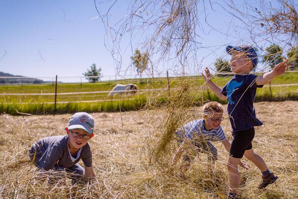 Kinder spielen im Stroh