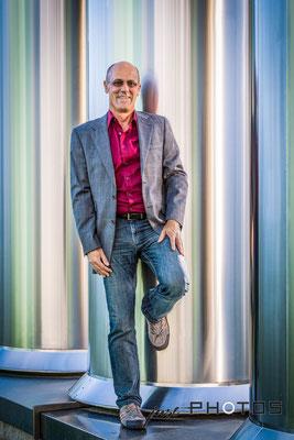 Mann in Jeans und mit Sakko lehnt lässig an silbernen Lüftungsrohren