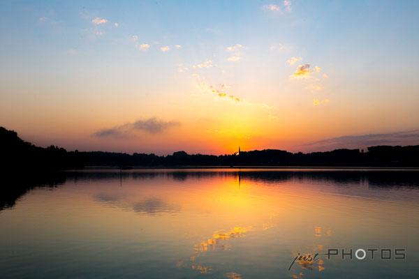 Sonnenaufgang am Wörthsee - die Sonne erscheint unmittelbar hinter dem Kirchturm von Steinebach