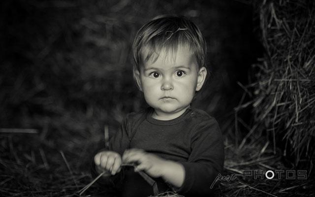 Kleines Kind sitzt im Heu (Stroh) und spielt an einem Halm
