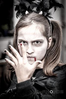 Halloween - Mädchen als Hexe mit weiß geschminktem Gesicht blickt mit grimmigem Gesicht