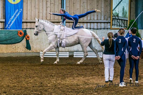 Voltigieren [ Turnier ] - Kind macht Fahne auf galoppierendem Pferd (Schimmel)