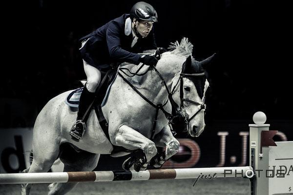 Munich Indoors - Springreiten - Pferd mit Reiter beim Sprung über ein Hindernis (Schwarz-Weiß)