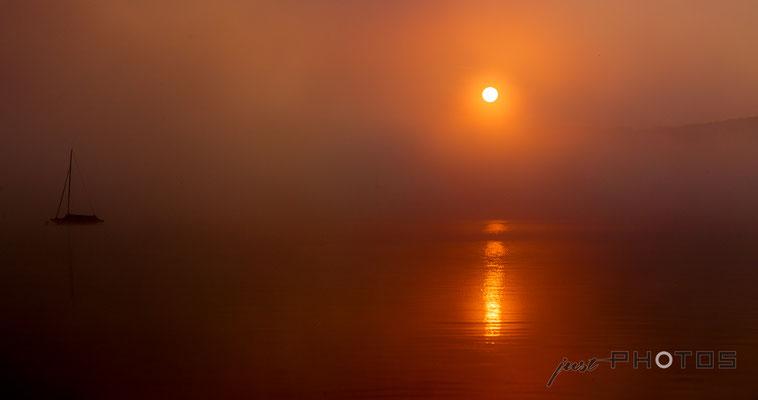 Ein Sonnenaufgang am Wörthsee in extremem Orange, die Sonne spiegelt sich im dunklen Wasser