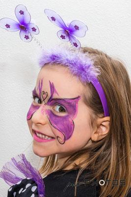 Mädchen - geschminkt mit lilia Schmetterling auf dem Gesicht