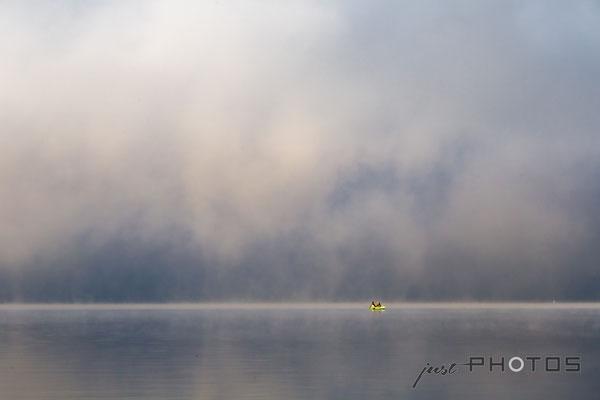 Dichter Nebel lichtet sich über dem Wörtsee, von der Sonne angestrahlt ein Fischerboot