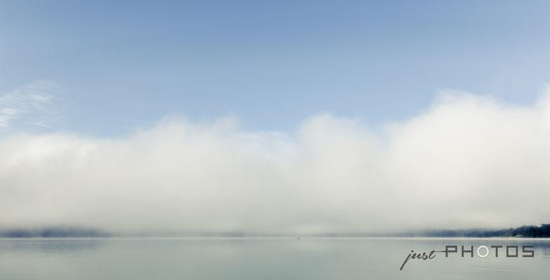 Nebelstimmung am Wörthsee, der Nebel steht wie Wolken über dem Wasser, in der Ferne ein Sportruderer