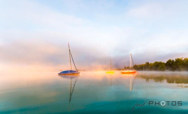 Segelboote im Wörthsee bei Nebel im Licht der aufgehenden Sonne