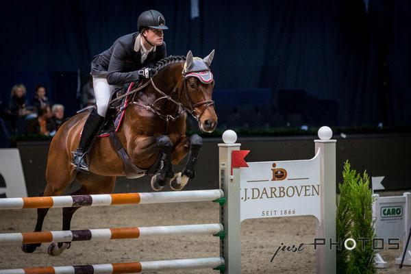 Munich Indoors - Springreiten - Pferd mit Reiter beim Sprung über ein Hindernis