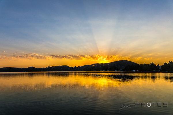 Sonnenstrahlen beim Sonnenaufgang am Wörthsee in Steinebach