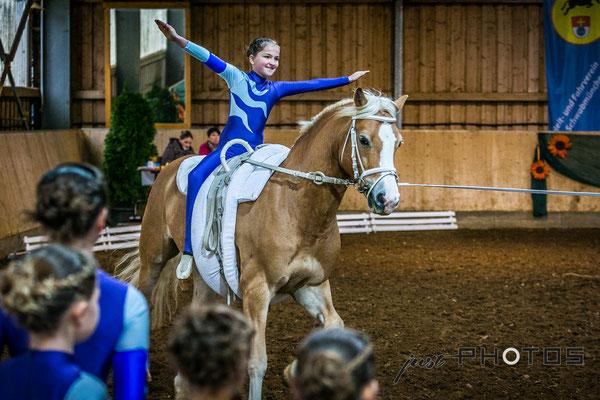 Voltigieren [ Turnier ] - Kind im Freisitz auf galoppierendem Pferd (Haflinger)