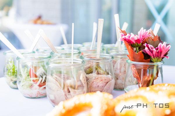 Finger-Food   Gläser mit Wurstsalat auf einem Bistro-Stehtisch   im Vordergrund Brezen und Blumen im Glas