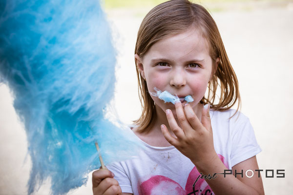 Mädchen isst hellblaue Zuckerwatte
