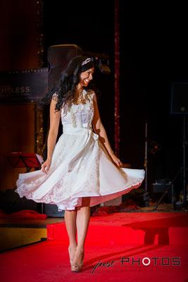 Frau | Model präsentiert ein weißes Brautkleid (Hochzeitskleid) auf einer Modenschau während einer Hochzeitsmesse für Brautmode