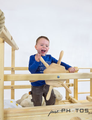 Junge steht in der oberen Etage an einem Spielbett (Abentheuerbett) und dreht mit Begeisterung an einem Holzlenkrad (Steuerrad)