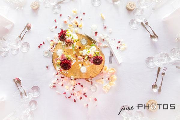 Hochzeit [ dekorierter Tisch von oben, in der Mitte Blumen auf Baumscheibe, weisse Tischdecke ]