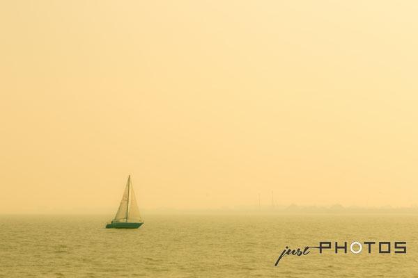Segelboot in gelbem Nebel (Dunst)