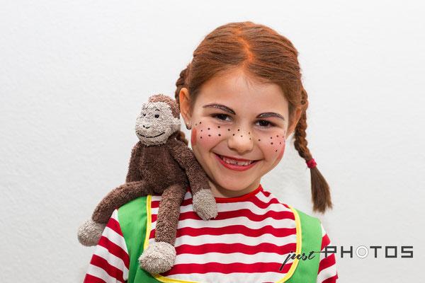 """Mädchen - mit roten Zöpfen und geschminkt als Pippi Langstrumpf mit Stoff-Affe """"Herr Nilsson"""" auf der Schulter"""