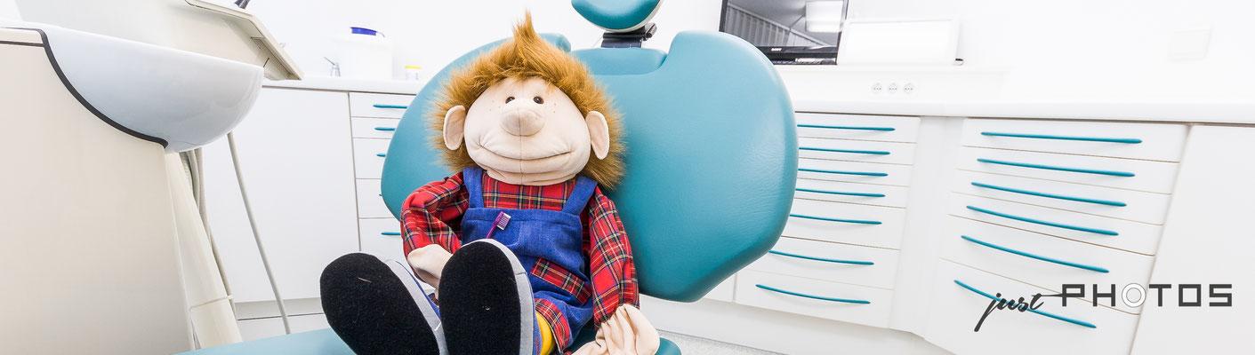 Auftragsarbeit für Zahnarztpraxis Dr. Georg Schulz: Kinderzahnheilkunde - eine große weiche Puppe sitzt auf einem Zahnarztstuhl [ Behandlungsstuhl in einer Zahnarztpraxis ]