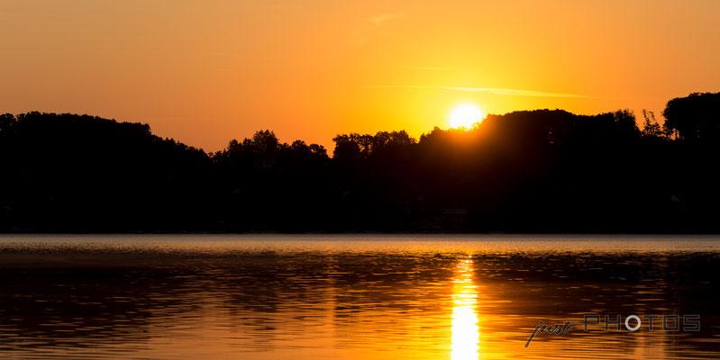 Sonnenaufgang am Wörthsee - die Sonne steigt hinter den Bäumen auf und spiegelt sich im Wasser