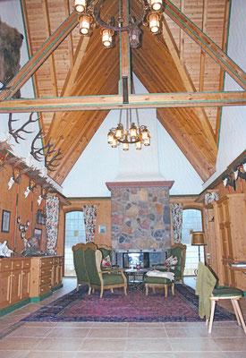 Offener Kamin, Sitzgarnitur und Untersicht des Dachstuhls mit gemalten und geschnitzten Verzierungen