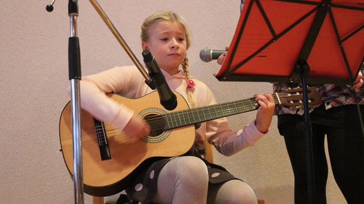 """Emmelie (10) spielt auf der Gitarre und begleitet mit Gesang: """"Runtergekommen, abgestiegen"""""""