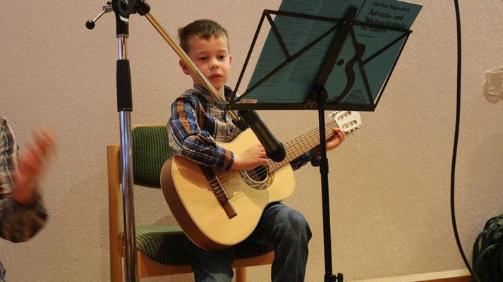 """Jonas (6) zupft an der Gitarre """"Wir sagen euch an...""""."""