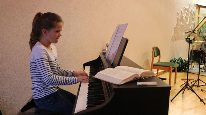 """Margarete (10) spielt am Klavier """"Im Korallenriff"""" von Karin Groß."""