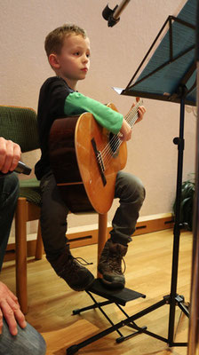 """Florian (7 ) zupft an der Gitarre """"Morgen kommt der Weihnachtsmann"""" ...."""
