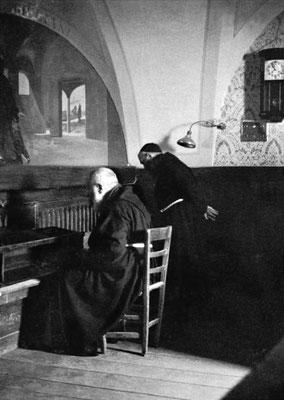 Padre Pio siede in raccoglimento davanti al Crocifisso; accanto a lui padre Onorato Marcucci da San Giovanni Rotondo, suo assistente personale