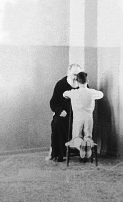 Un bambino si inginocchia davanti al Padre, verosimilmente in preparazione della sua Prima Comunione