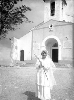 Una ragazza posa per la foto-ricordo in occasione della sua Prima Comunione. Sullo sfondo, la facciata della chiesa di Santa Maria Incoronata del Monte