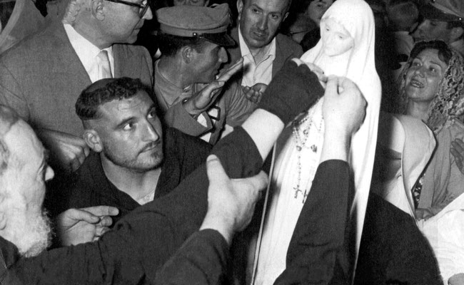 Padre Pio, in quel momento infermo, viene aiutato ad offrire una corona del Rosario, ricevuta in dono dal Gruppo di preghiera di San Casciano Val di Pesa, alla venerata immagine della Madonna Pellegrina