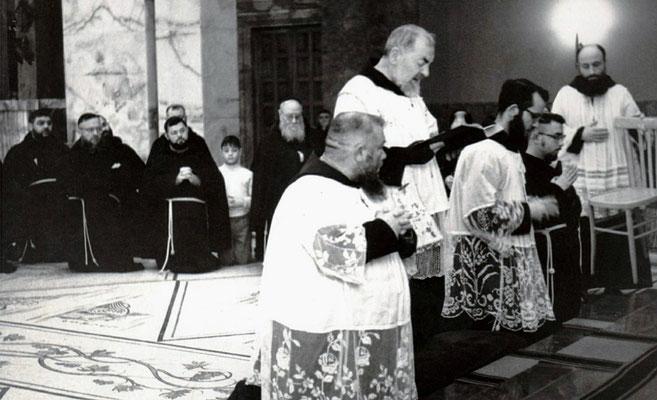 Padre Agostino, seduto, al centro della foto, assiste a una funzione religiosa presieduta dal suo antico allievo