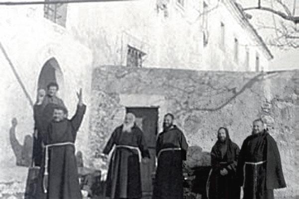 """Padre Pio (seduto), ritratto insieme ad alcuni confratelli, nei pressi del c.d. """"arco"""" del convento di San Giovanni Rotondo"""