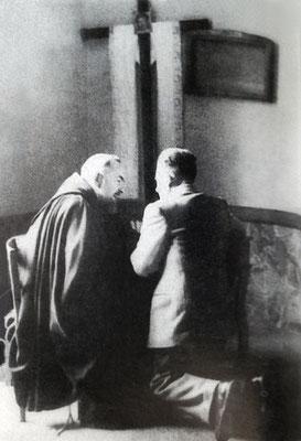 Un uomo genuflesso sull'inginocchiatoio, in un angolo della vecchia sagrestia