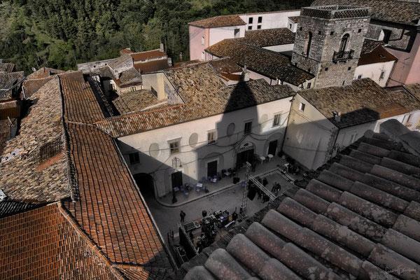 In alto a destra, la torre Galuppi, ex Campanile della Chiesa di S. Francesco; dietro, intuibile il quadrato del Chiostro del Convento; al centro, la piazza Duomo, sulla quale il campanile della Cattedrale proietta la sua ombra