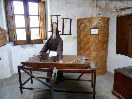 Una madia per impastare il pane; dietro, un silo in cui veniva depositato il grano, ricevuto durante la questua