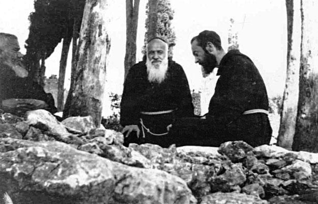 Con due confratelli, seduto lungo il viale dei cipressi nell'orto del convento (1919)