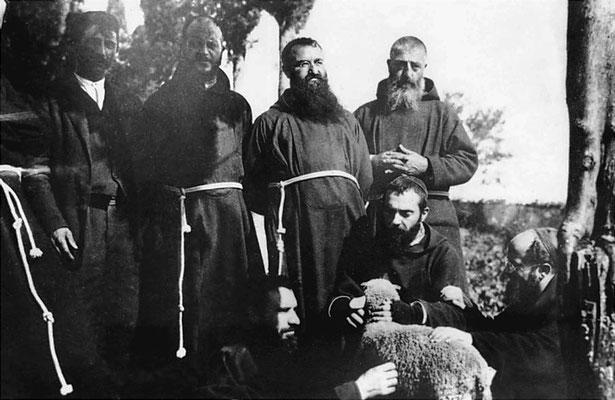 Padre Pio che accarezza una pecora; 1° a destra, padre Luigi d'Avellino; a sinistra, padre Raffaello da San Giovanni Rotondo; dietro, da destra: fra Fedele Colavita, padre Pietro da Ischitella, padre Anastasio da Roio, Emanuele Brunatto