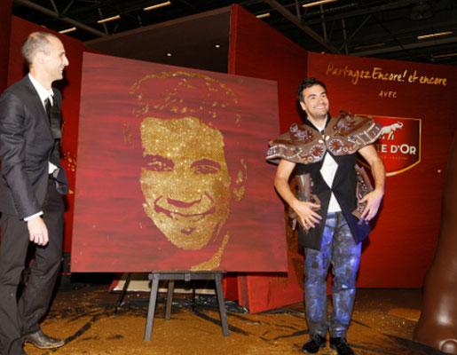 Alex Goude prend la pose à côté de son portrait glitter