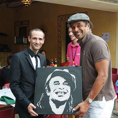 EriK Black remet à Yannick Noah son mini-portrait à l'issue du live painting en ouverture de concert - Festival de Poupet 2015 - France